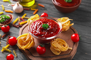Bowl with tasty tomato sauce and pasta on wooden board
