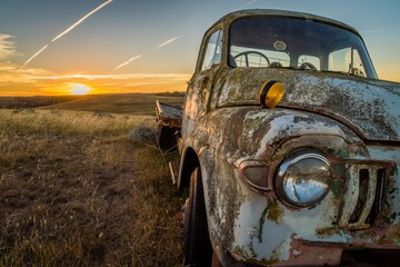Abandoned wreck car in a field in Australia at sunset