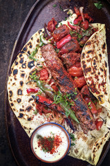 Traditional Adana Kebap with tomato and salad on a flatbread on a plate