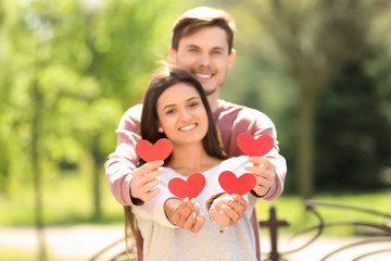 Portrait of lovely couple with paper hearts outdoors