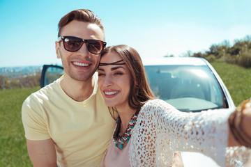 Smiling girlfriend. Smiling girlfriend wearing stylish accessories making photo with her handsome boyfriend
