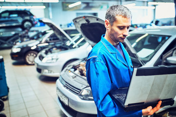 mechanic man with automotive diagnostic scanner and clipboard checking car system at workshop
