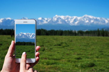 Woman's hand is holding smartphone and take a photo of mountains.