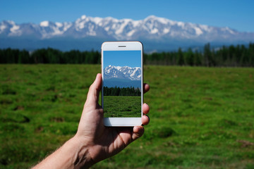 Man's hand is holding smartphone and take a photo of mountains.