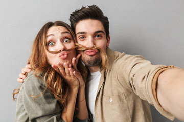 Portrait of a funny young couple hugging taking a selfie