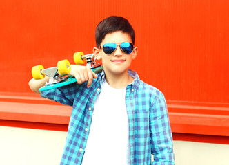Fashion portrait teenager boy holds a skateboard in sunglasses on red background