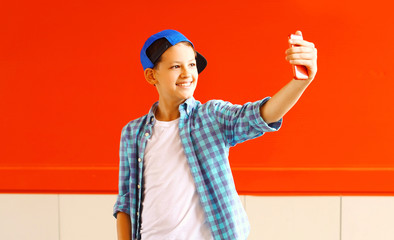 Fashion smiling cool teenager boy is taking picture self portrait on a smartphone