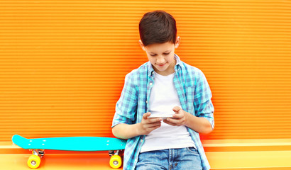 Fashion teenager boy uses smartphone, skateboard on a colorful orange background