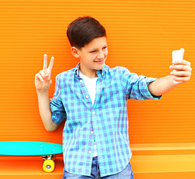 Fashion cool teenager boy is taking picture self portrait on a smartphone