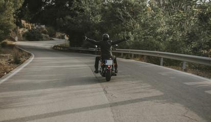 Man raising arms up while rides his black motorcycle.