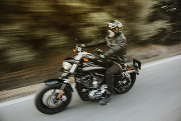 Blurry motion image of man riding a black American motorcycle on the road.