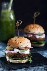 Veggie falafel burgers with fresh vegetables on dark background