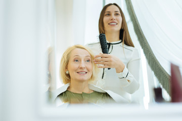 Positive emotions. Delighted happy woman being in a wonderful mood while visiting a beauty salon