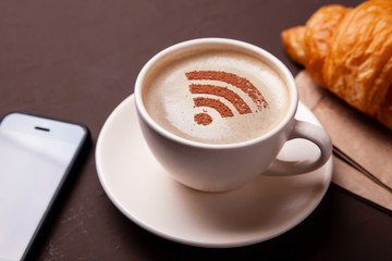 Cup of coffee with WiFi sign on foam. Free access point to the Internet WiFi. I like coffee break with croissant