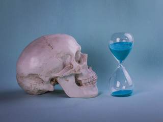 Skull with a sand clock. Concept of life and death with hourglass and skull. Sand running. Relatively and time concept.