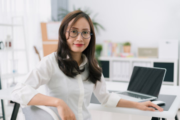 Happy young businesswoman with glasses working on computer laptop in home office