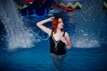 Sexy red haired girl in black swimsuit having rest in swimming pool of aqua park.