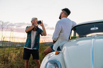 Man taking photo of man with car