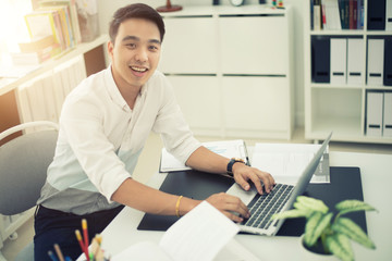 Asian young businessman working at his office.