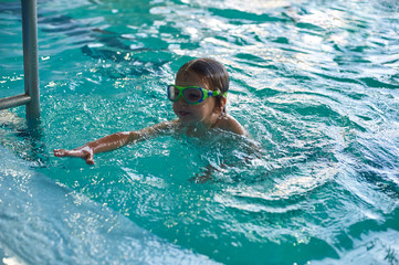 Little smiling boy swims in the pool. Close-up.