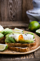 Poached egg and sliced avocado on whole wheat bread toast