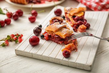 Board with pieces of delicious homemade cherry pie on white wooden table