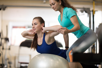 Fitness trainer helping young woman doing back exercises in gym
