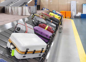 Suitcases on luggage conveyor belt at arrival area of airport