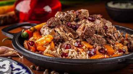 Uzbek traditional cuisine. Pilaf or plov with lamb, and red garnet, in an iron cast-iron frying pan kazan. Background image. Copy space, selective focus