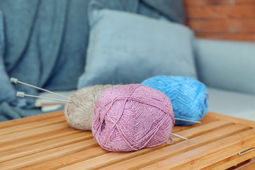 Colorful knitting yarn on wooden crate in room