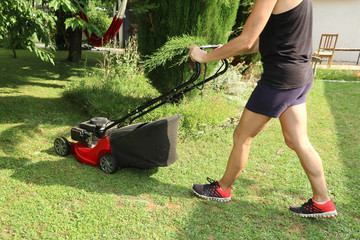a woman is passing the mower in the garden