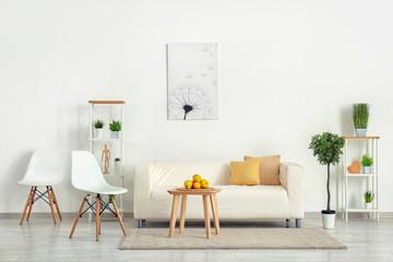 Stylish furniture with comfortable sofa near light wall