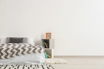 Big comfortable bed with shelf unit near light wall