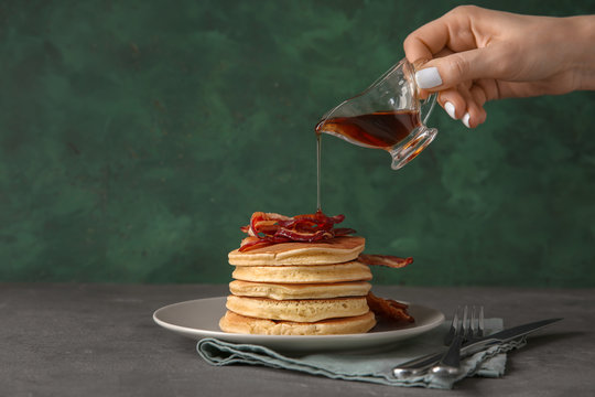 Woman pouring maple syrup onto tasty pancakes with fried bacon