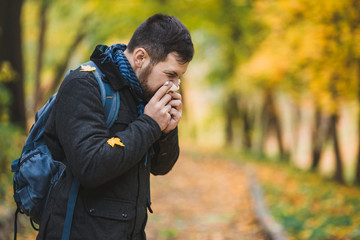 man sneezes and blows his nose in a handkerchief in an autumn park