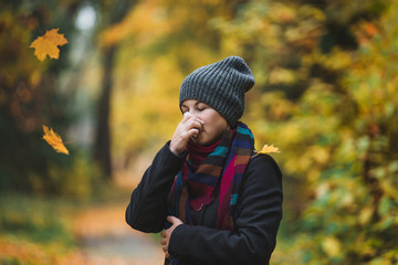 Woman sneezes and blows his nose in a handkerchief in an autumn park