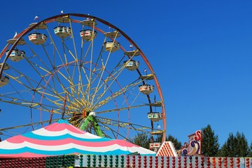 Ferris wheel with blue sky background and colorful tents in foreground Wall mural