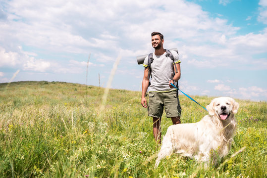traveler with backpack walking with golden retriever on summer meadow with cloudy sky
