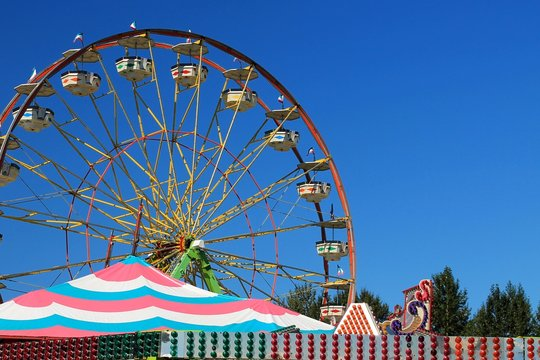 Ferris wheel with blue sky background and colorful tents in foreground