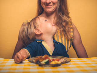 Little toddler at table eating with mother