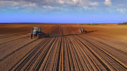 Farmers in tractors seeding, sowing agricultural crops in field at sunset