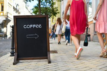 Coffee sign on wooden black chalkboard in street