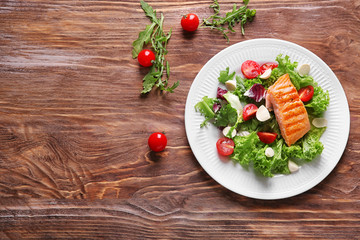 Plate with tasty grilled fish and fresh salad on wooden table