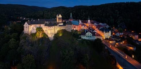 Aerial, night view on Loket Castle ( Hrad Loket, Burg Elbogen ) 12th-century Gothic style castle on a massive rock with illuminated medieval city Loket. Tourist spot near to Karlovy vary, Czechia.