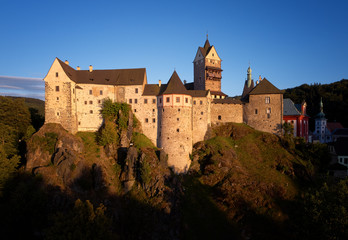 Aerial view on Loket Castle, Burg Elbogen, 12th-century Gothic style castle on a big rock, massive fortification illuminated by setting sun. Tourist place close to Karlovy vary, Czech republic.