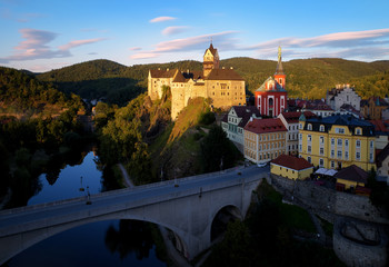 Aerial view on Loket Castle, Burg Elbogen, gothic style castle surrounded by medieval city and green hills, massive fortification illuminated by setting sun. Close to Karlovy vary, Czech republic.