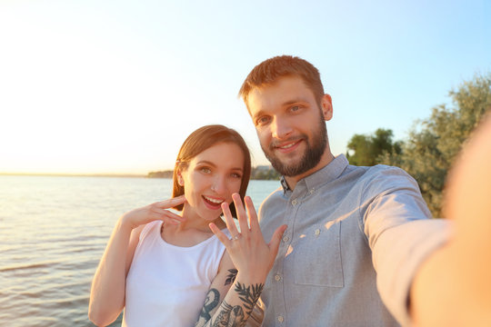 Happy couple taking selfie with engagement ring near river on sunny day
