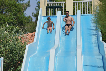 Father and son going down water slide, filming themselves