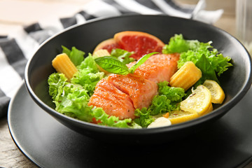 Bowl with fresh salad and fish on table, closeup