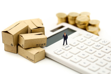 Miniature people : Businessman and box with  coins  and Calculator of tax,shipping, rent container, business concept.